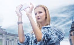 muchacha Rubio-cabelluda, tomando imágenes en el smartphone, sosteniéndolo con ambas manos, fondo del cielo Día, al aire libre Fotos de archivo