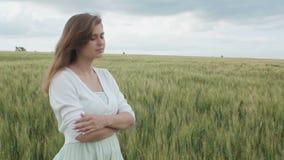 Muchacha rusa joven hermosa entre las espiguillas verdes altas del trigo en el campo Mujer joven que disfruta del verano, armonía metrajes