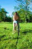 Muchacha saliente con su bicicleta Foto de archivo libre de regalías