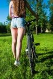 Muchacha saliente con su bicicleta Fotos de archivo