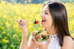 Muchacha sana que come la ensalada al aire libre con el campo de flor en backgrou Foto de archivo