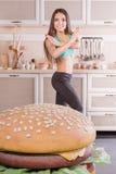 Muchacha sana que lucha contra la hamburguesa Imagenes de archivo