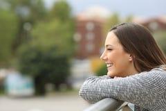 Muchacha satisfecha que mira lejos de un balcón Fotos de archivo