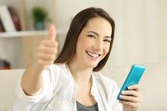 Muchacha satisfecha que sostiene el teléfono elegante con los pulgares para arriba Fotografía de archivo libre de regalías