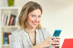 Muchacha satisfecha que sostiene un teléfono elegante que le mira Imagenes de archivo