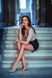 Muchacha sensual que se sienta en las escaleras y la sonrisa fotos de archivo libres de regalías