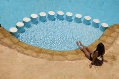 Muchacha sentada por una piscina. imagen de archivo