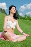 Muchacha serena meditating en hierba fotografía de archivo