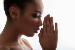 Muchacha serena que sostiene las palmas juntas delante de cara Imagen de archivo