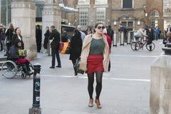 Muchacha seria con el pelo rizado en falda roja que camina abajo de la calle Imagen de archivo
