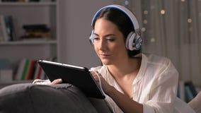 Muchacha seria con los auriculares que buscan medios en la tableta