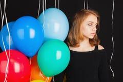 Muchacha seria con los globos coloridos sobre negro Fotos de archivo