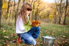 Muchacha seria en el bosque con las hojas y el compartimiento Fotos de archivo