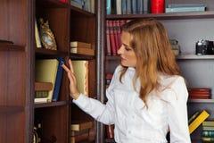 Muchacha seria en la biblioteca que busca un libro fotos de archivo libres de regalías