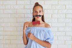Muchacha seria en la ropa casual que presenta con los accesorios de papel encendido Foto de archivo