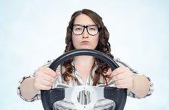 Muchacha seria en vidrios con el volante del coche, concepto auto Fotografía de archivo libre de regalías