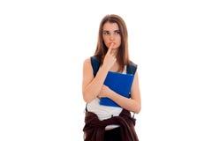 Muchacha seria joven del estudiante con las carpetas azules para los cuadernos en la presentación de las manos aislados en el fon Fotografía de archivo libre de regalías