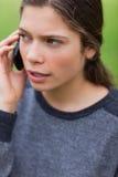Muchacha seria joven que habla en el teléfono Imagen de archivo libre de regalías