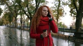 Muchacha seria joven que habla en su teléfono móvil en mientras que camina en el parque del otoño Mujer cabelluda rizada al usar  metrajes