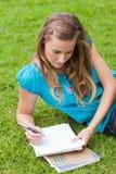 Muchacha seria joven que miente en la hierba en un parque Imagen de archivo