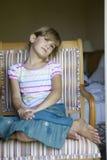 Muchacha seria linda que se sienta en silla Fotografía de archivo