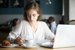 Muchacha seria que estudia en el café que hace las notas que se preparan para el examen Fotografía de archivo