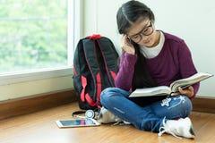 Muchacha seria que lee un libro para el examen en sala de clase Imágenes de archivo libres de regalías