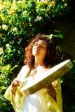 Muchacha shamanic hermosa que juega en el tambor del marco del chamán en fondo con las hojas y las flores imagen de archivo libre de regalías