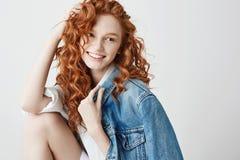 Muchacha sincera joven con la mirada sonriente roja del pelo rizado en lado sobre el fondo blanco Copie el espacio Imagen de archivo libre de regalías