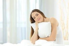 Muchacha sincera que sostiene una almohada y que le mira en una cama Fotografía de archivo libre de regalías