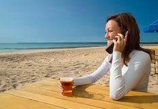 Muchacha sitting&talking por el teléfono en una playa Fotos de archivo