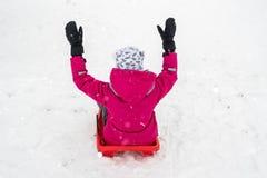 Muchacha sledding en la colina Imágenes de archivo libres de regalías