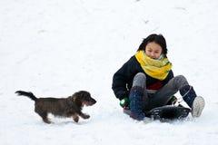 Muchacha sledging con su perro Imagen de archivo libre de regalías