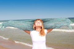 Muchacha smilling feliz en la playa con la bufanda Imagenes de archivo