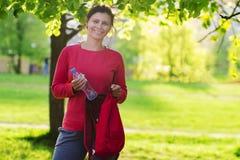 Muchacha smilling hermosa en ropa de deportes en parque verde el día soleado con la botella de agua y de mochila fotos de archivo libres de regalías
