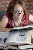 Muchacha smirking mientras que lee Imagenes de archivo