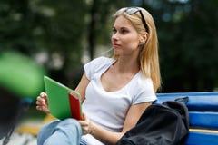 Muchacha soñadora con la tableta en sus manos que se sientan en banco Foto de archivo