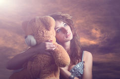 Muchacha soñadora con un oso de peluche Imagen de archivo libre de regalías