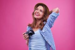 Muchacha soñadora con una cámara en las manos que miran hacia arriba Foto de archivo libre de regalías