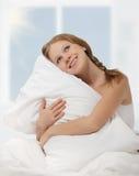 Muchacha soñadora de la belleza que abraza la almohadilla mientras que en cama Fotografía de archivo libre de regalías