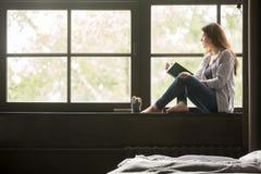 Muchacha soñadora pensativa que sostiene el libro que se sienta en travesaño en casa Imagen de archivo libre de regalías