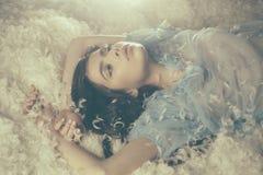 Muchacha soñadora que miente en el montón suave de las plumas blancas Pelusa blanca que abraza suavemente a la hembra hermosa jov Fotos de archivo