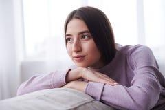 Muchacha soñadora que se relaja en el sofá en casa Imagenes de archivo