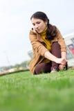 Muchacha soñadora que se sienta en una hierba en un cielo y una construcción del fondo Imagen de archivo libre de regalías