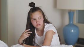 Muchacha soñolienta irritada que se sienta en la cama, intentando recuperarse después de sueño almacen de video