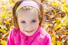 Muchacha sobre las hojas de otoño amarillas Imagenes de archivo