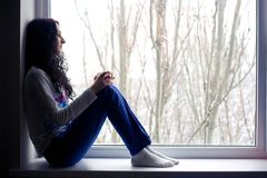 Muchacha sola cerca de la ventana con la taza Foto de archivo libre de regalías