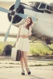 Muchacha sola con la maleta en el aeroplano cercano. fotos de archivo libres de regalías