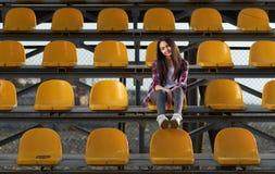 Muchacha sola de la animadora que se sienta en soportes y sonrisas dulce Fotos de archivo