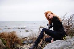 Muchacha sola en costa azotada por el viento Imagen de archivo libre de regalías